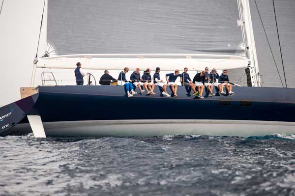 With the wind beginning to fill the high-tech sails, the yacht's crew gets comfortable on the weather rail.